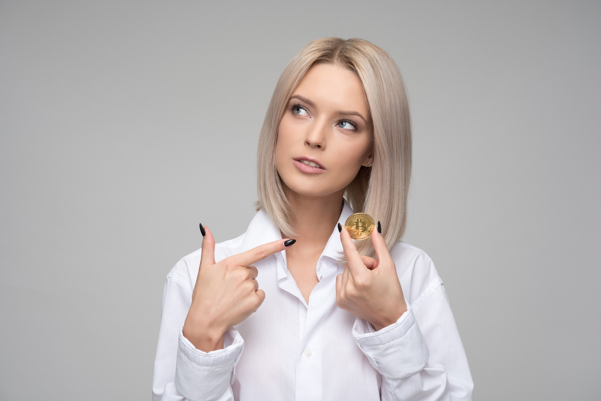 A lovely blond woman pointing to the Bitcoin coin that she holds.
